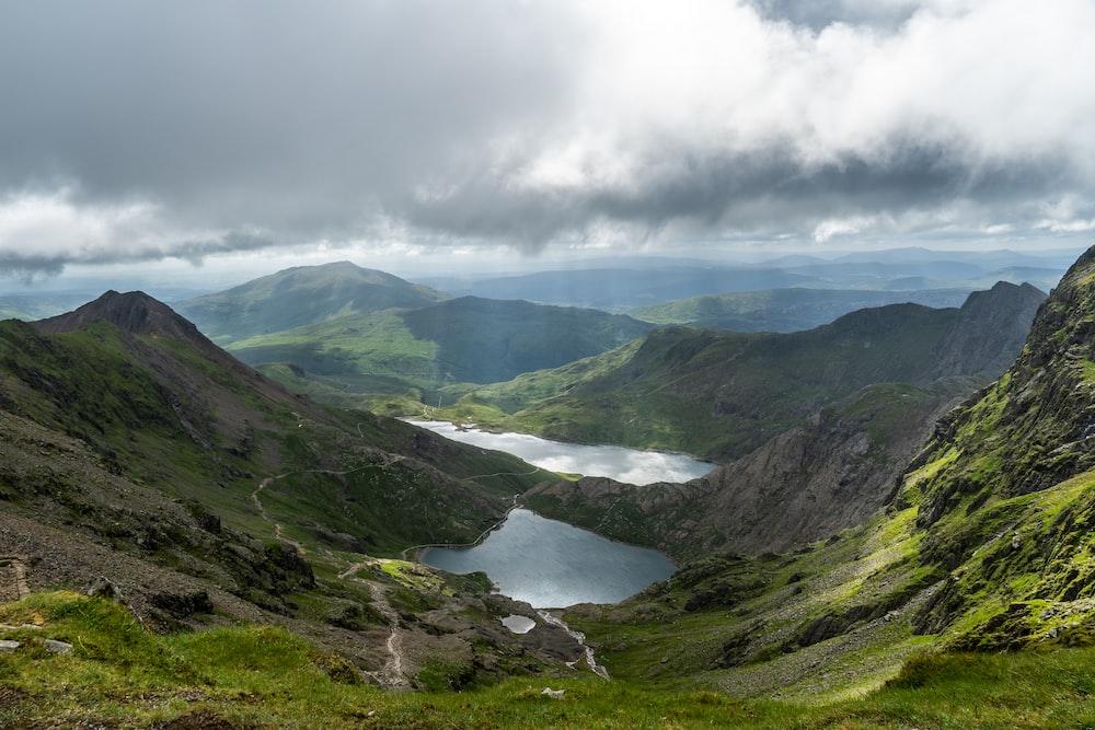 lake beside mountain under cloudy sky