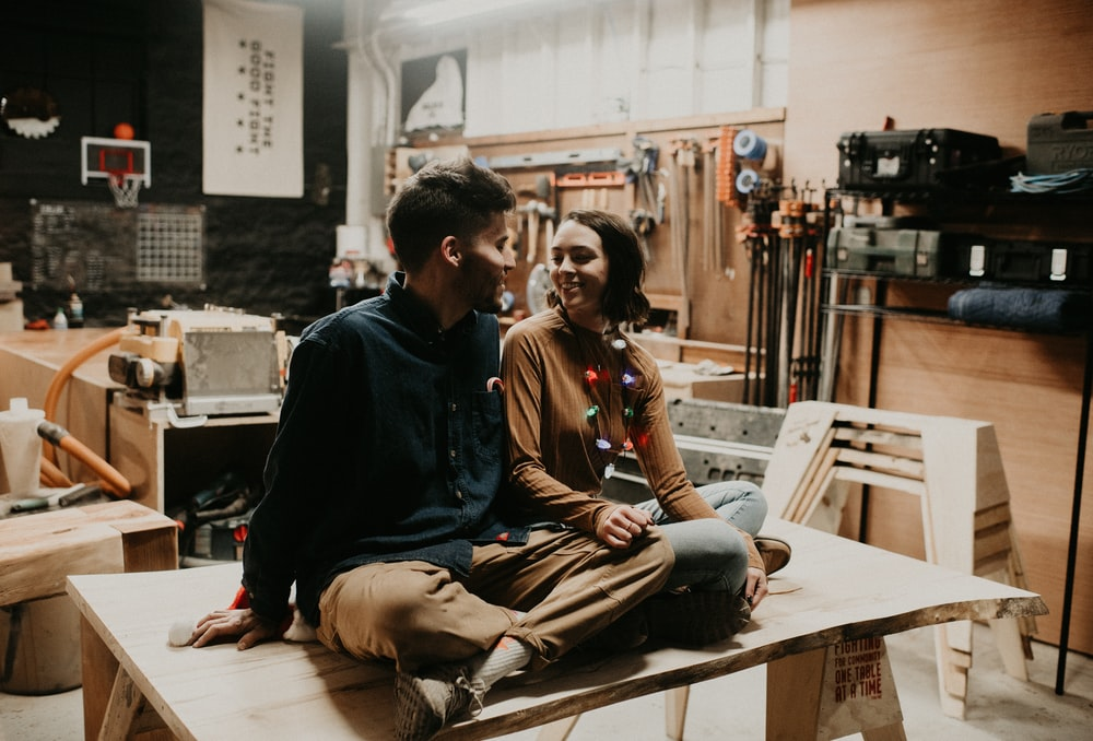 man and woman smiling and facing each other while sitting on table indoors