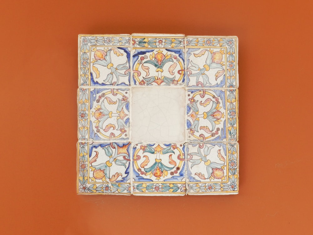 square blue and multicolored wall decor on orange wall