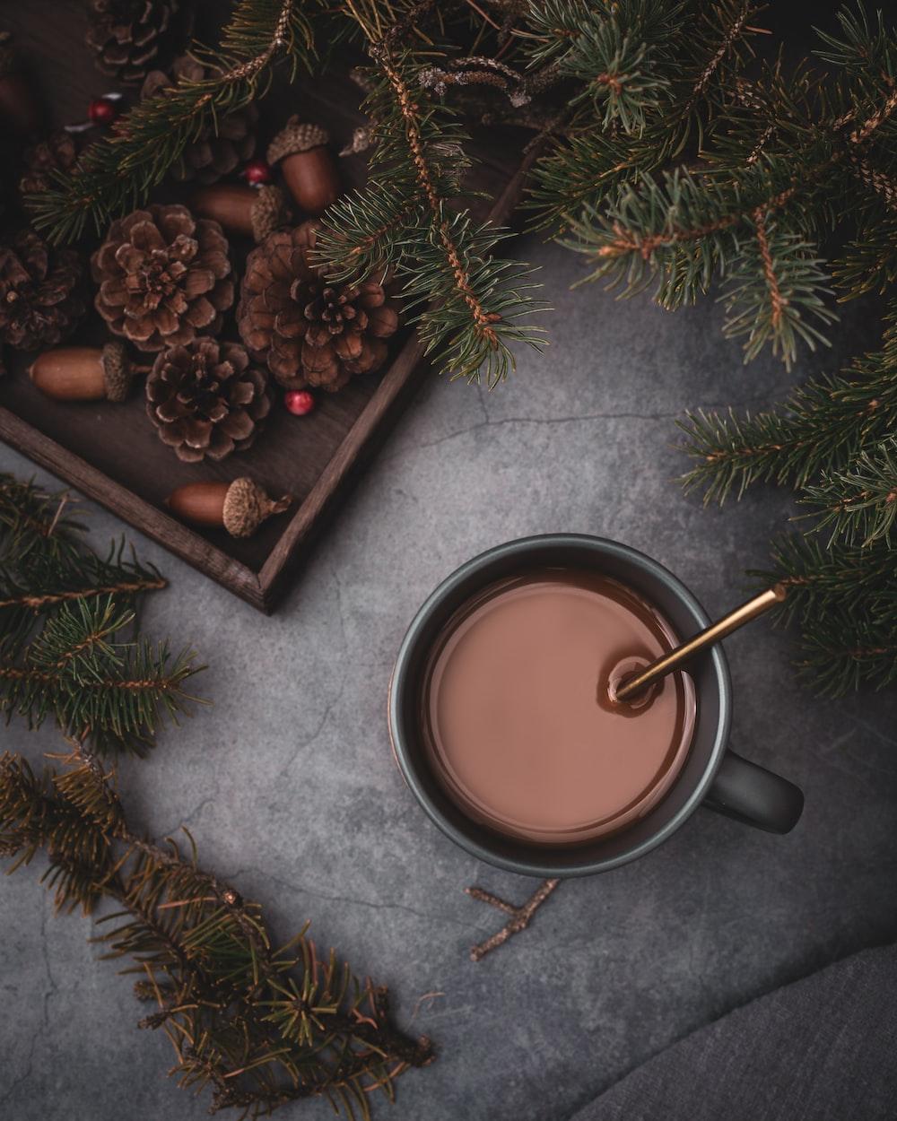 full mug beside pinecones