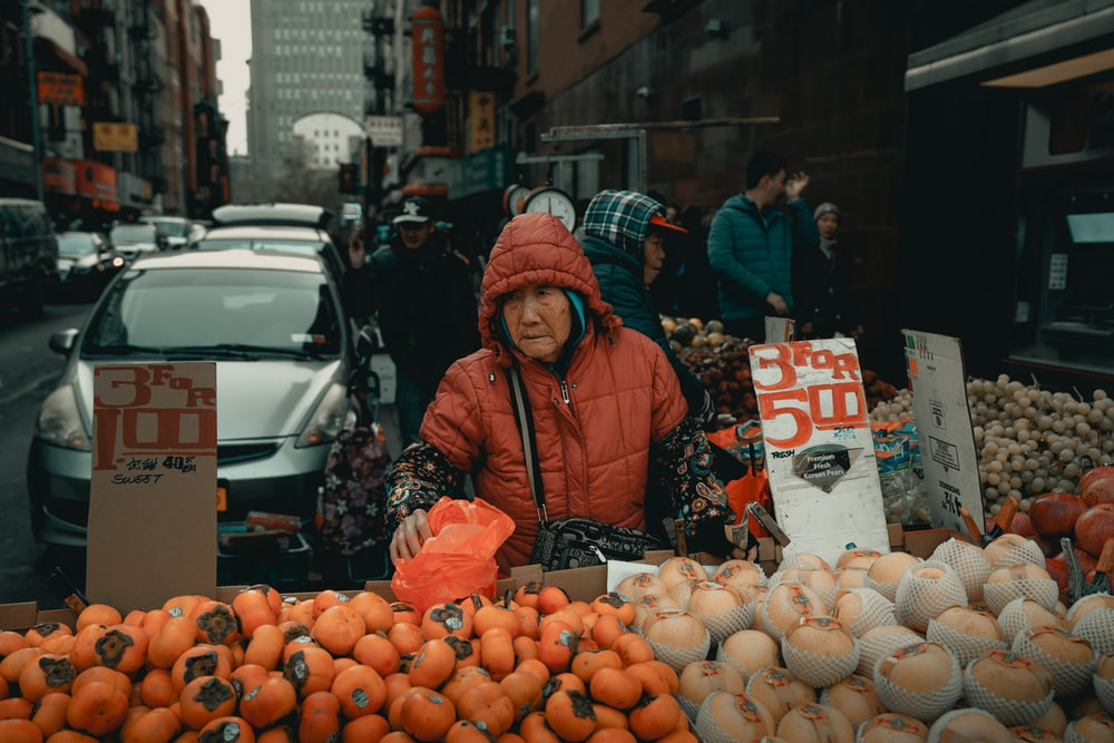 Woman selling fruits near park vehicle on street during day time