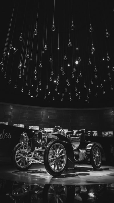 grayscale photography of vintage vehicle in museum