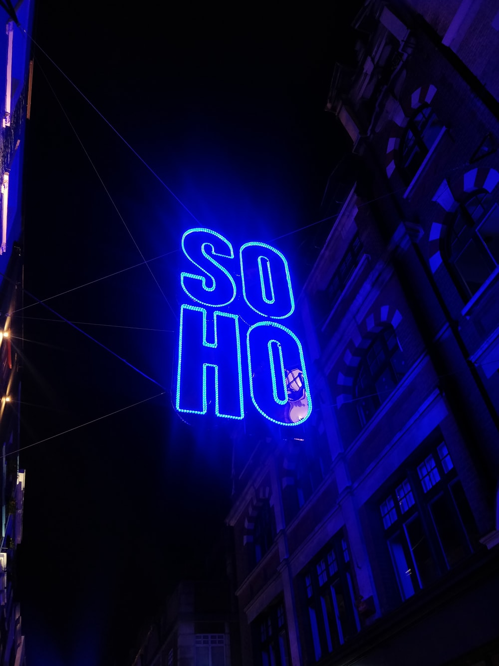 blue Soho LED sign outside building during night time
