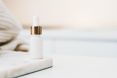 white drop bottle on white surface beauty teams background