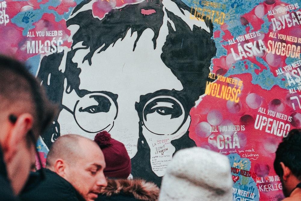 people near wall with graffiti art of John Lennon