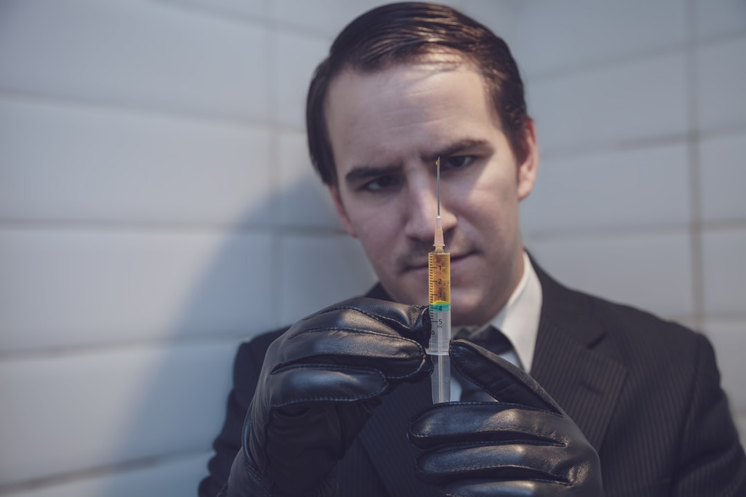 Hitman holding a syringe with a drip of liquid