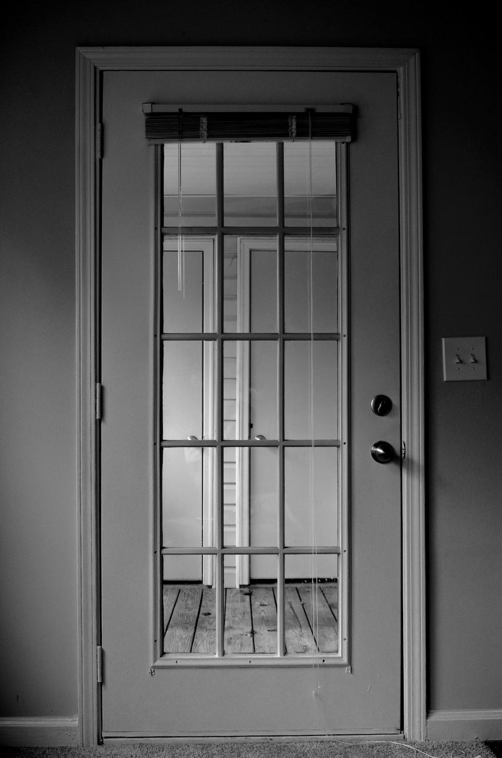 grayscale photo closed lite door