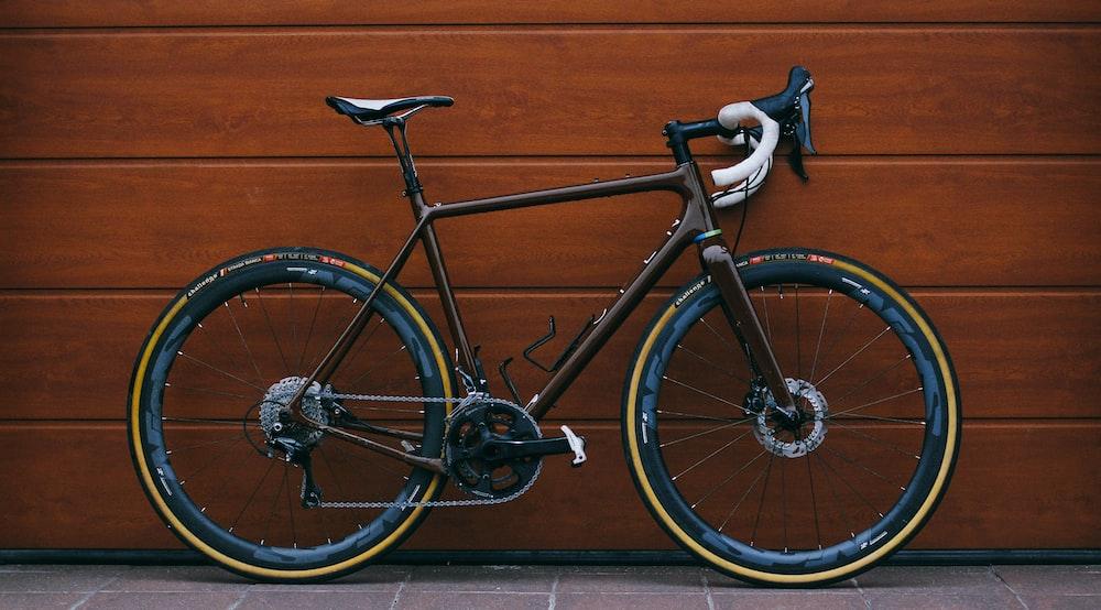 black road bike against wooden wall
