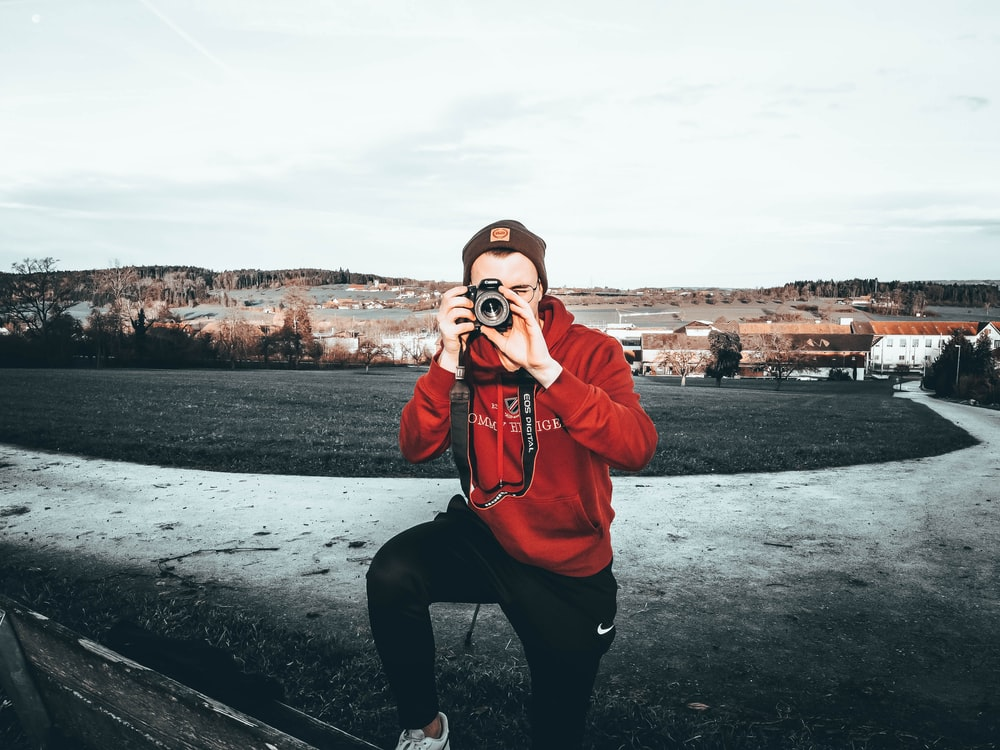 man using camera on field during day