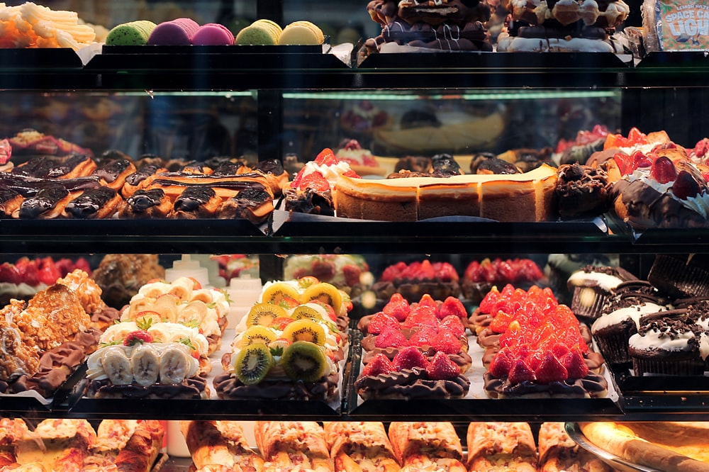assorted cakes displaying in glass cabinet