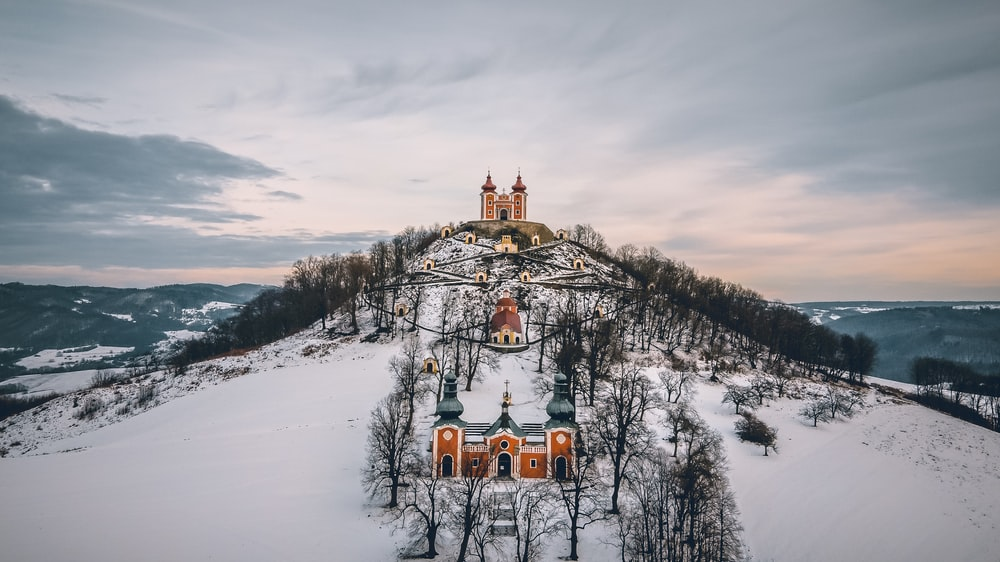 brown and gray church on snowy field viewing mountain under white and gray sky