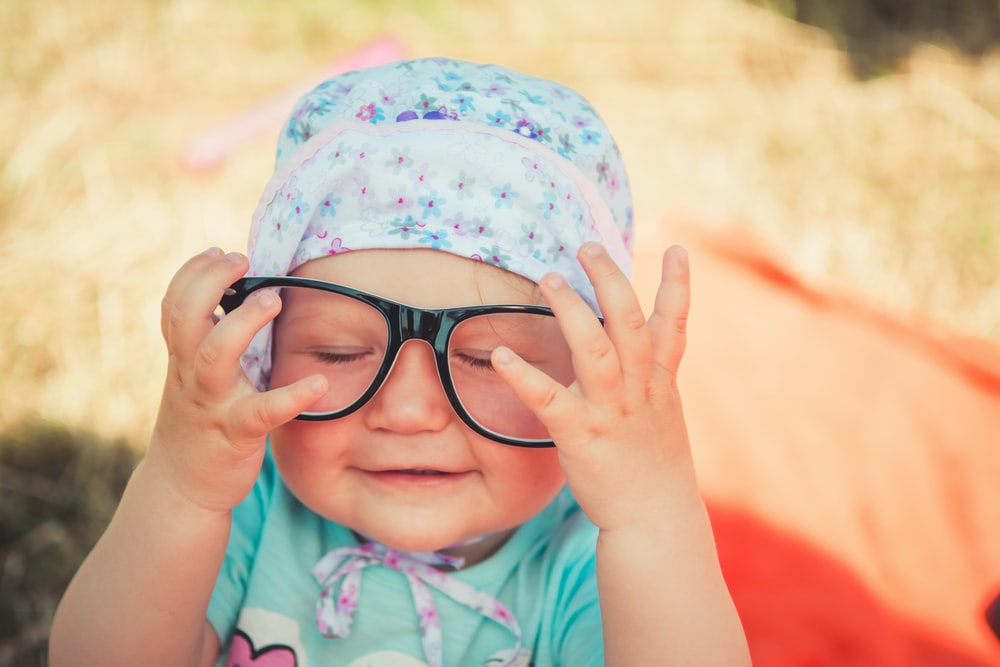 selective focus photography of baby wearing eyeglasses