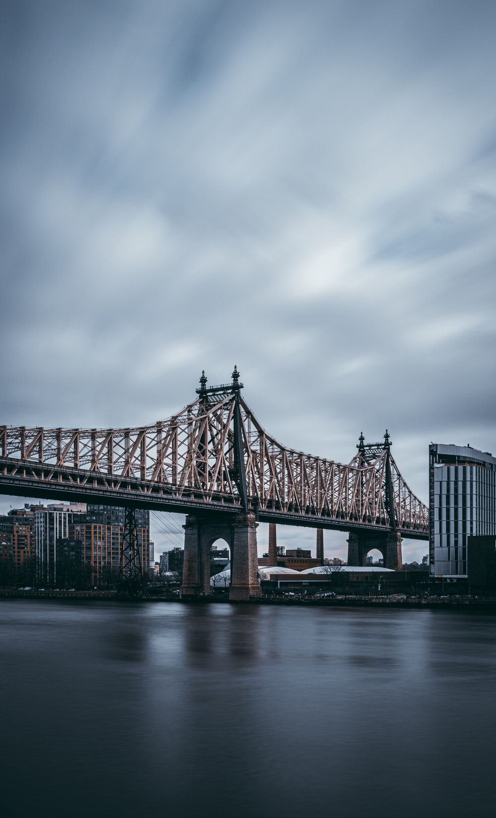shallow focus photo of bridge under cloudy sky