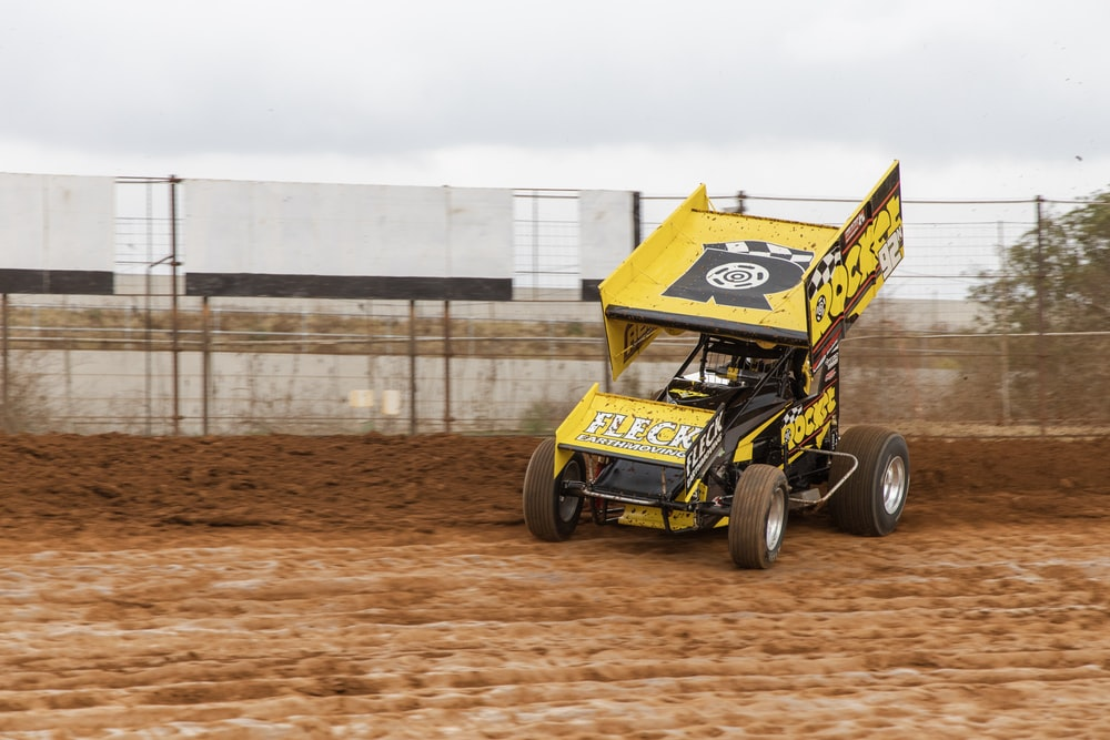 yellow Sprint car racing at the race track