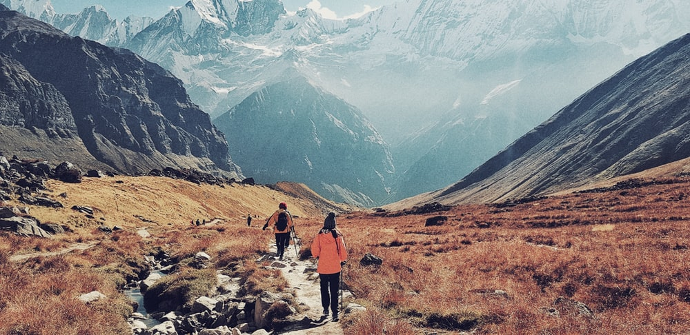 woman and man running near mountains