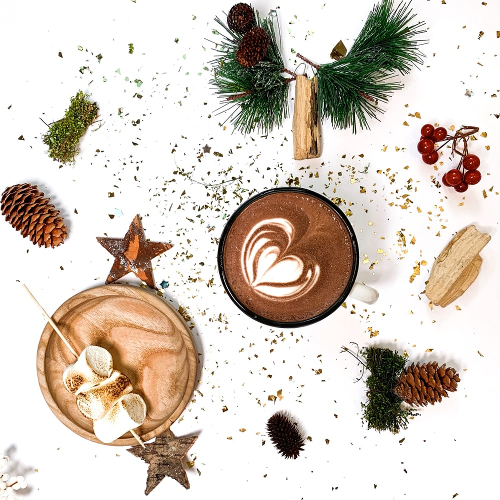 pine cone, star, and green leaves with cup of coffee