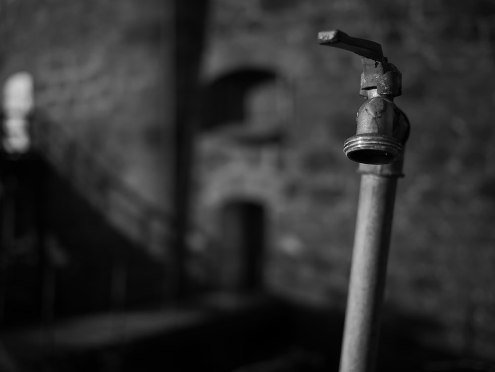 grayscale photography of faucet