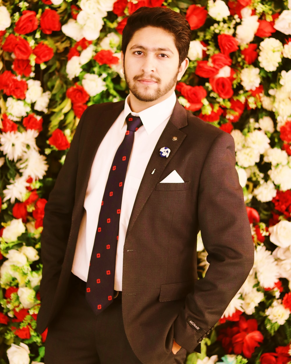 man in black suit standing in front of red and white flower bouquet