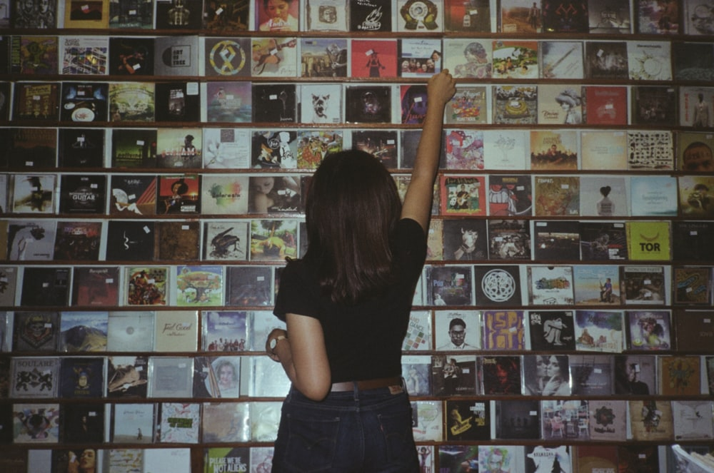 woman wearing black t-shirt standing while facing back and reaching CD album