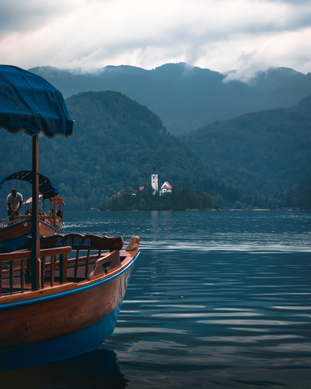 brown and blue wooden boat floating in water