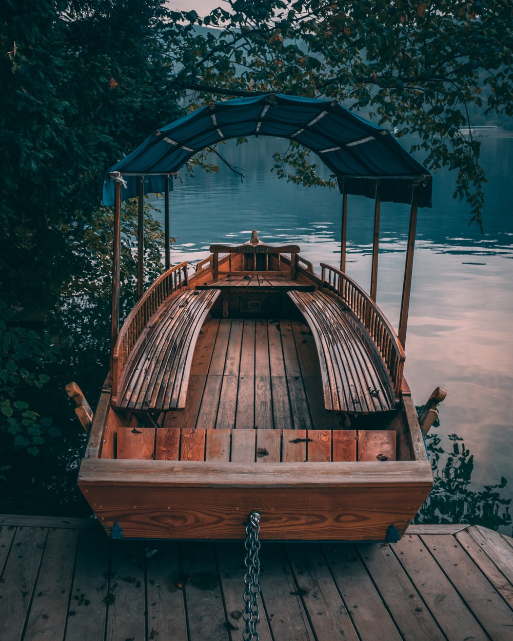 brown wooden boat near body of water and wooden dock surrounded with green trees