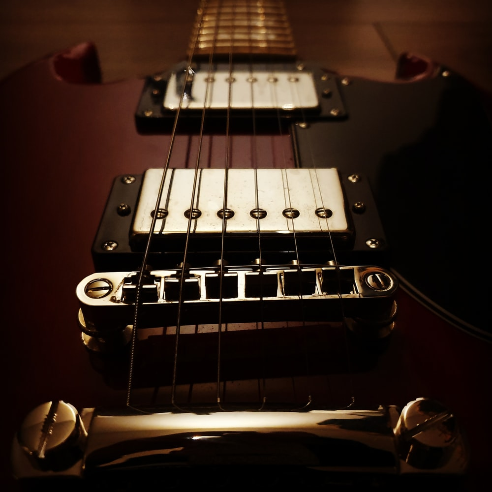 macro photography of brown electric guitar
