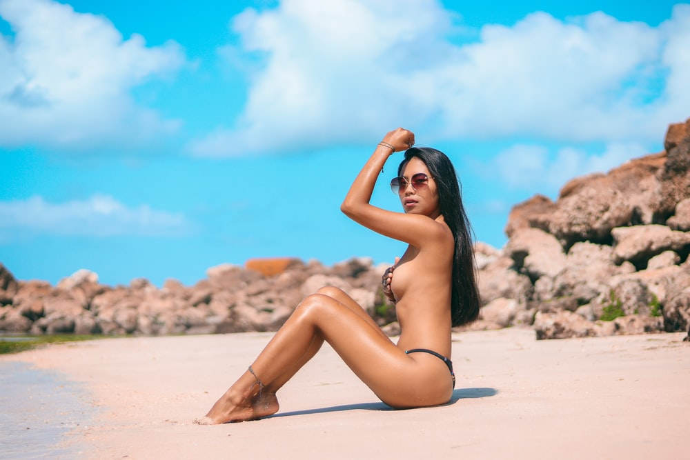 woman wearing grey bikini sitting on the sand