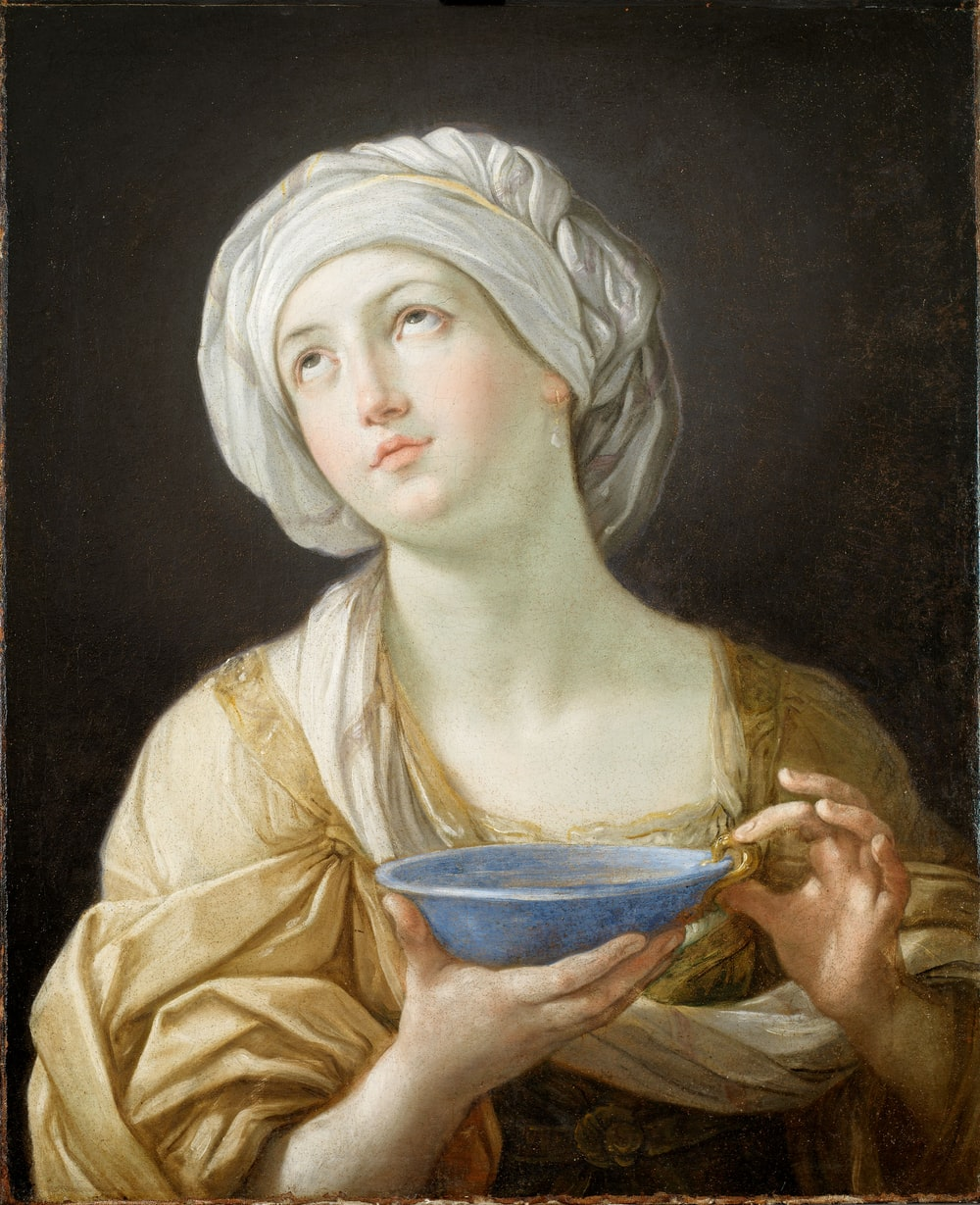 woman wearing white headdress while holding blue bowl painting