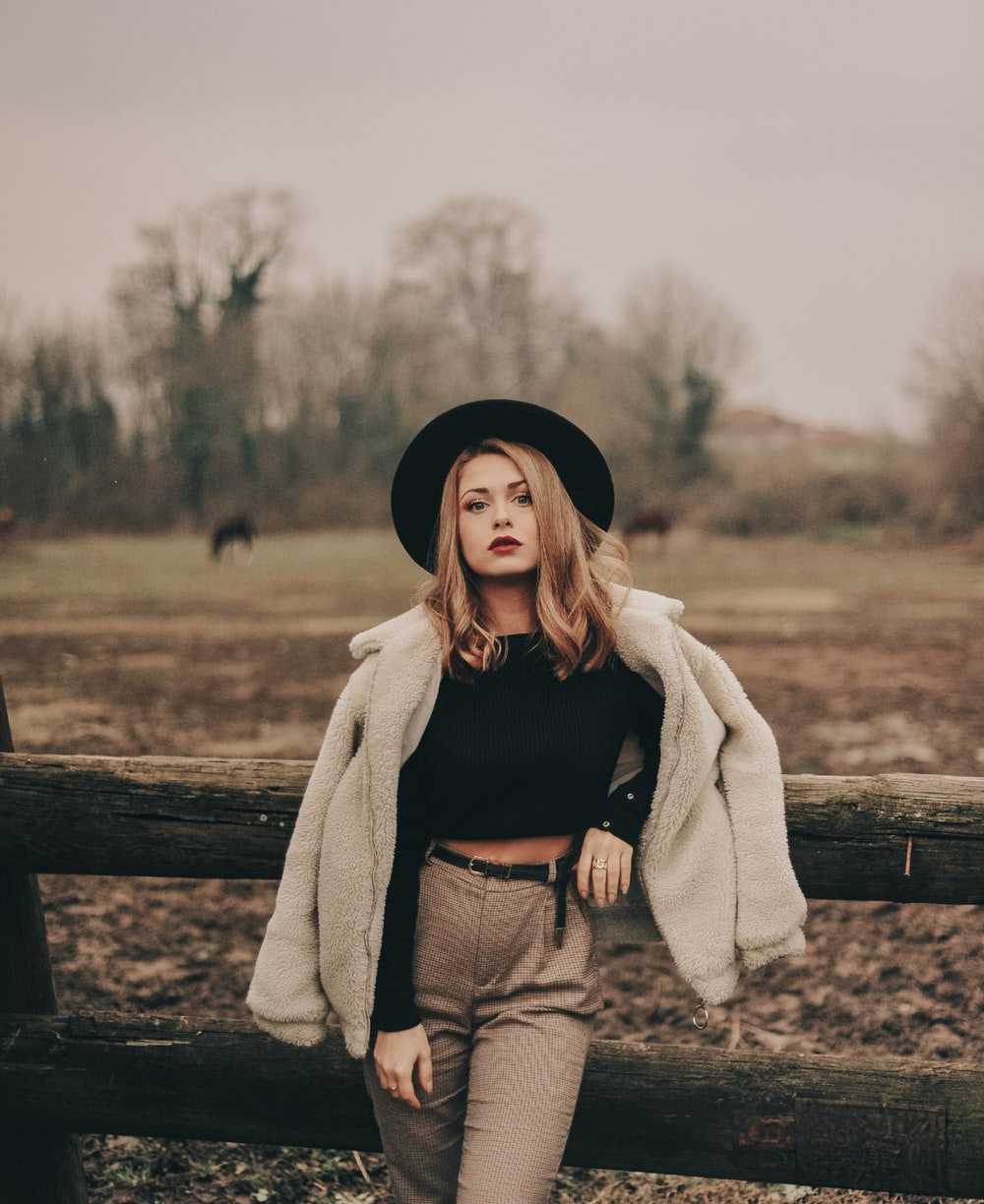 woman in black crop top and brown pants leaning on log fence