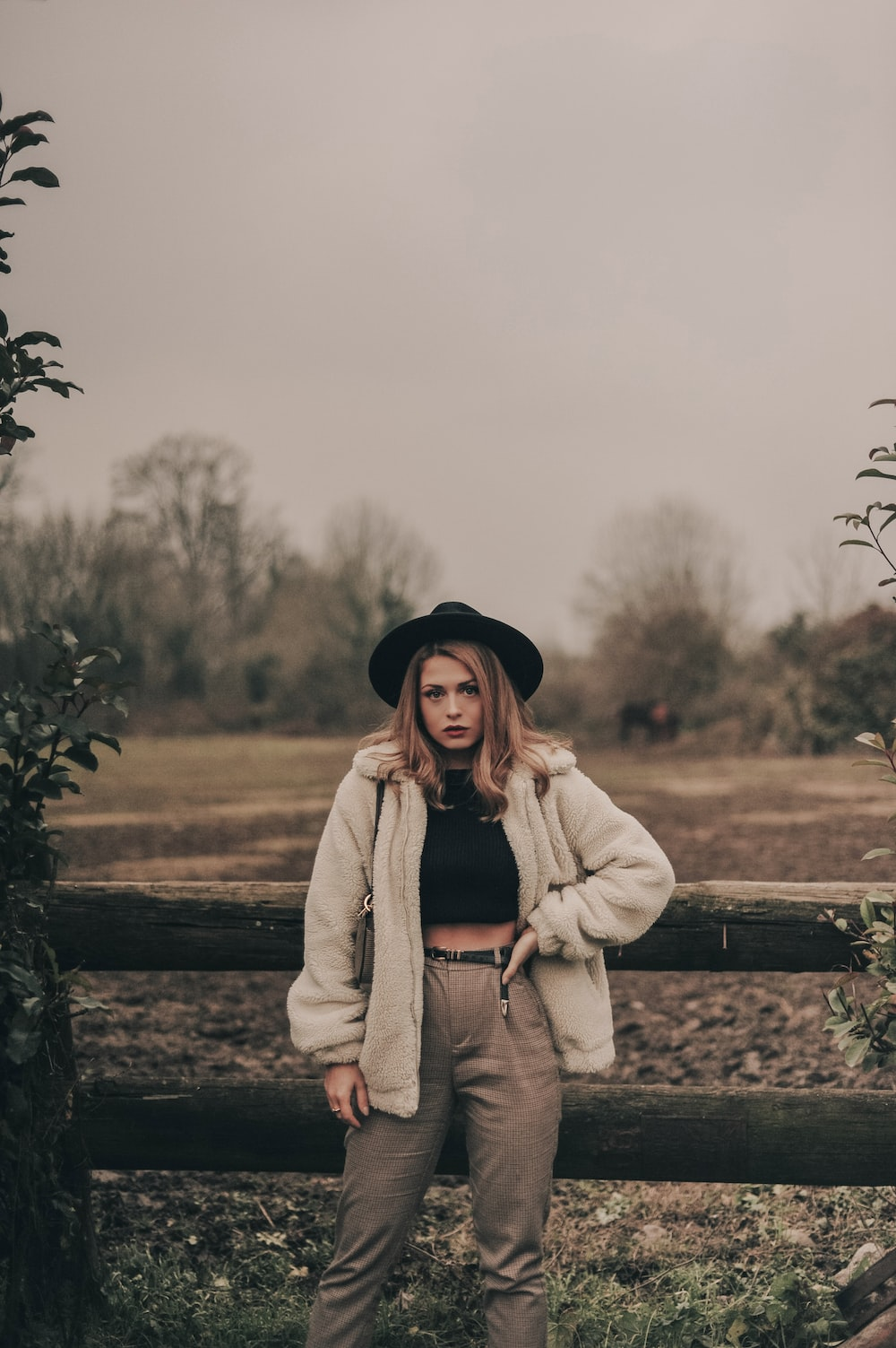 woman in coat and hat standing beside fence