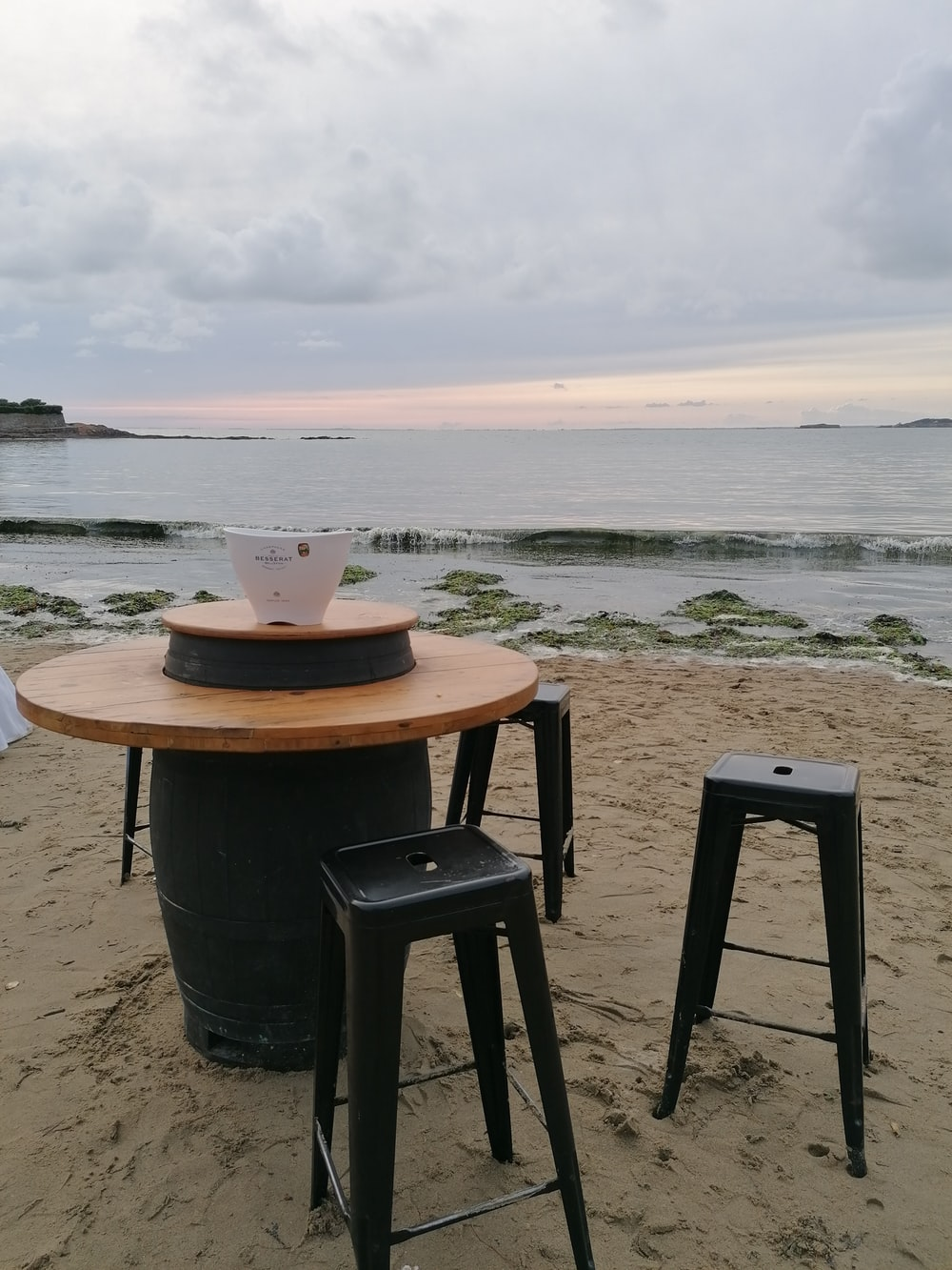 round black and brown table beside three black stools on shore during day