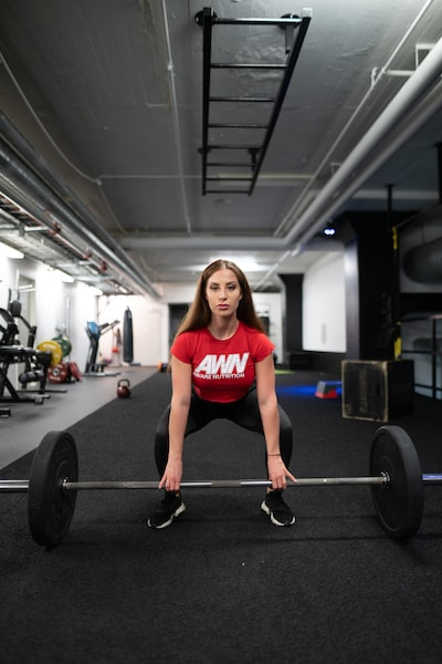 woman squatting and holding barbell inside gym
