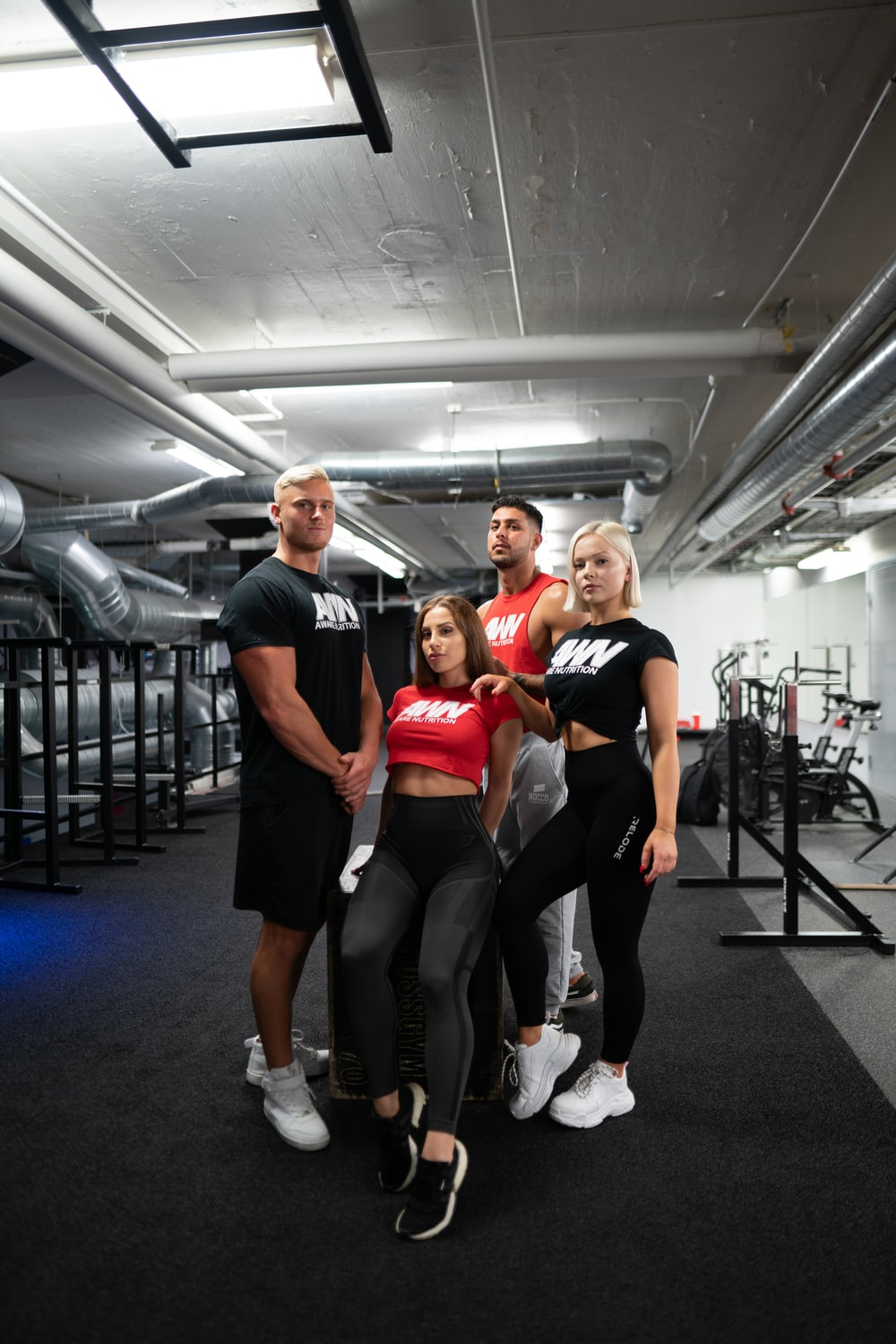 two men standing behind two women inside gym