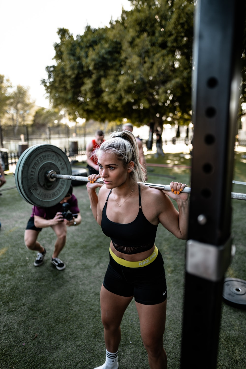 woman lifting a barbell on her back