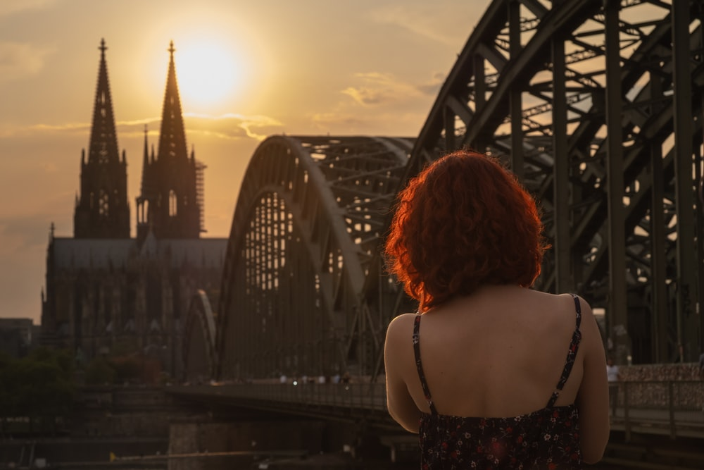 woman wearing black and multicolored spaghetti strap top standing while facing back near Cologne Cathedral in Germany