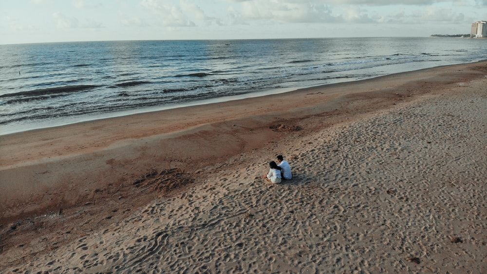 two people sits on sand beside seashore during daytime