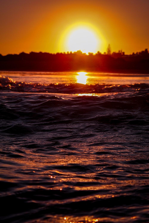 Fotografía macro de cuerpo de agua bajo un cielo naranja