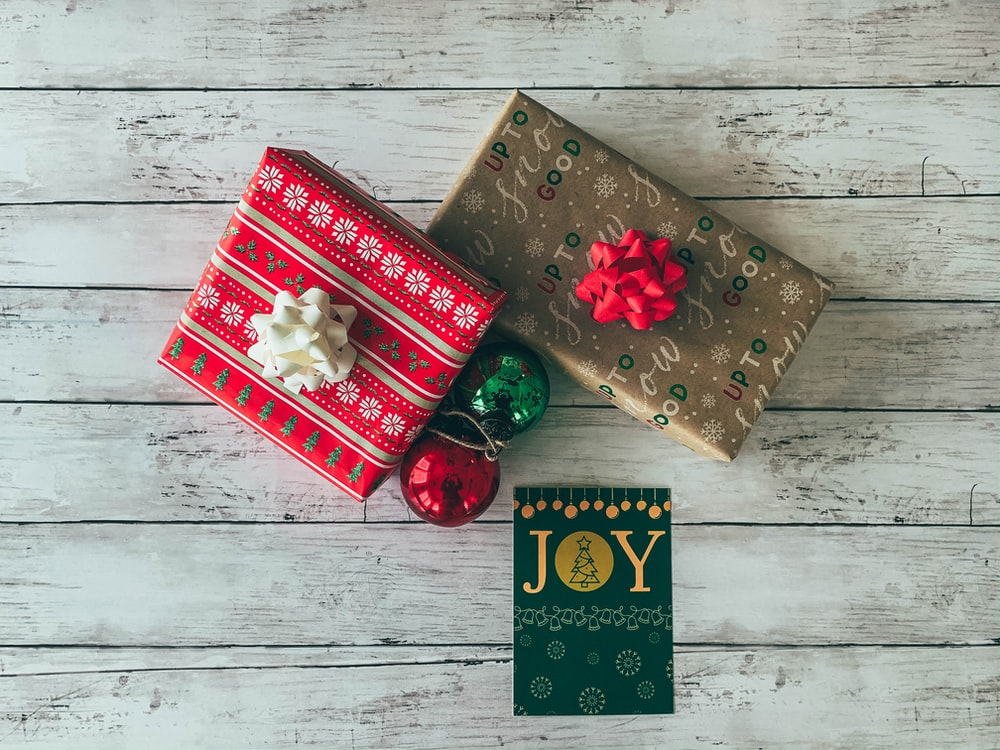 gift boxes beside Joy card and baubles on white surface