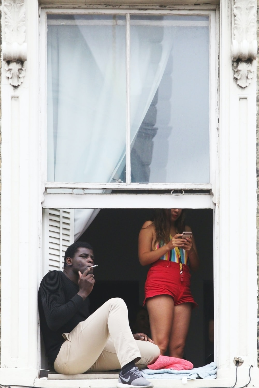 man wearing black crew-neck sweatshirt smoking cigarette stick while sitting near open window near woman using phone standing