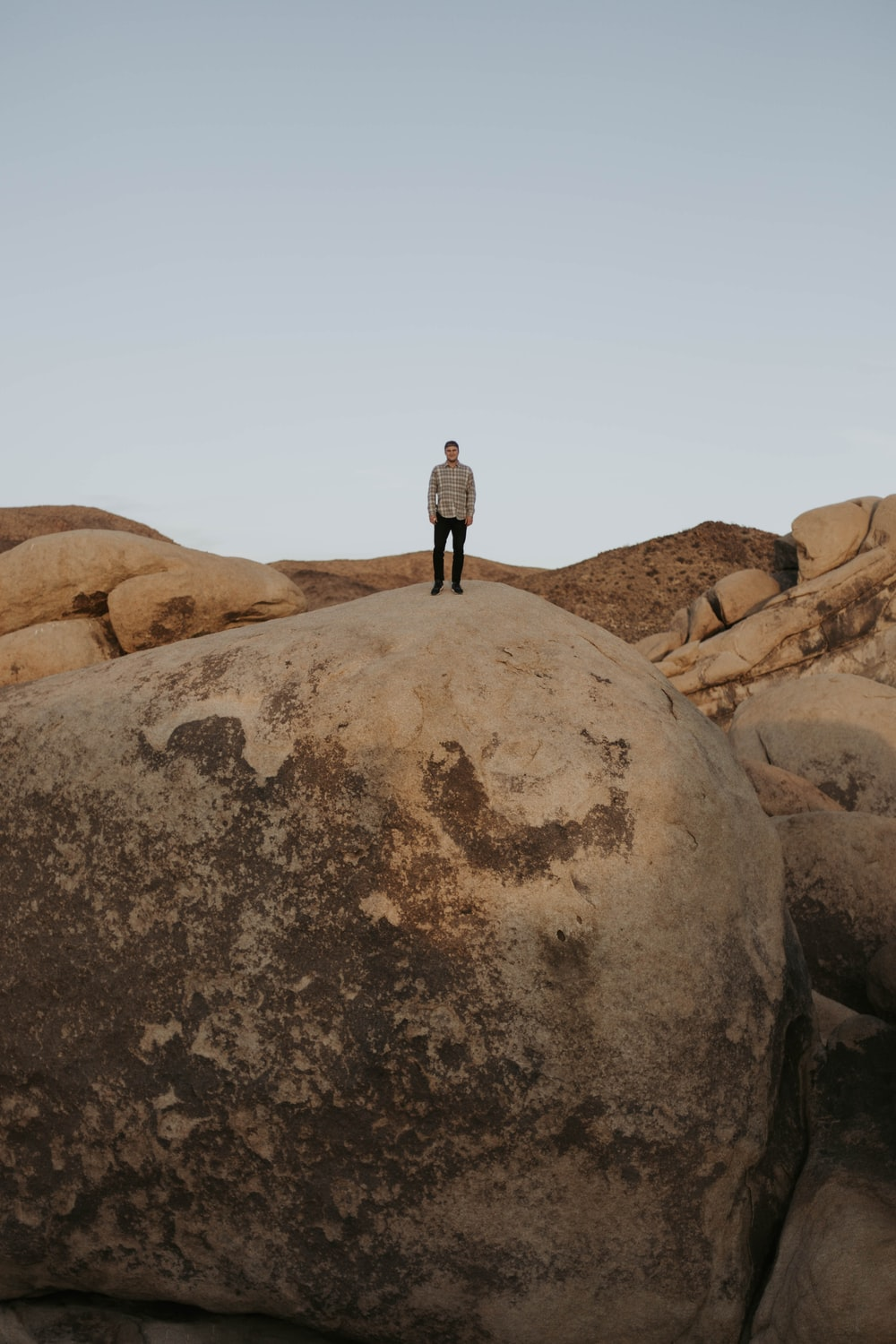 man standing on cliff during daytime