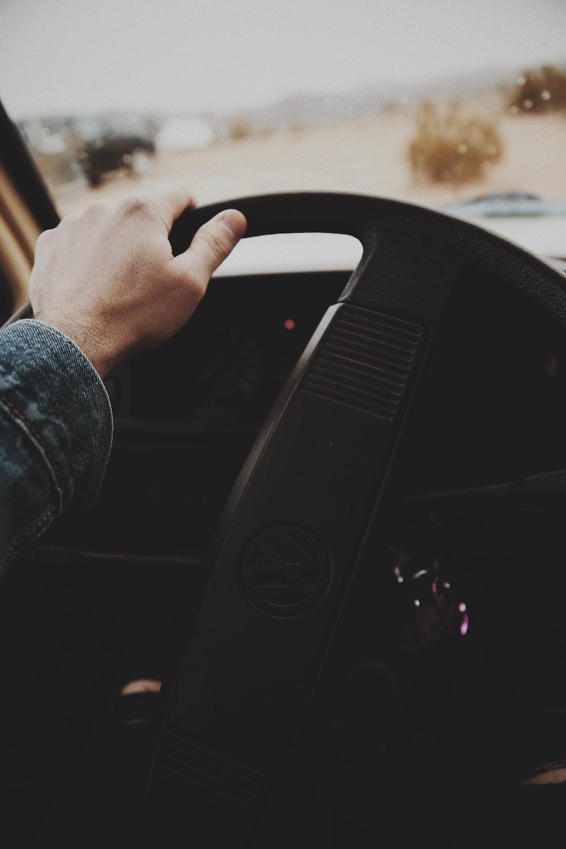 person holding Volkswagen steering wheel