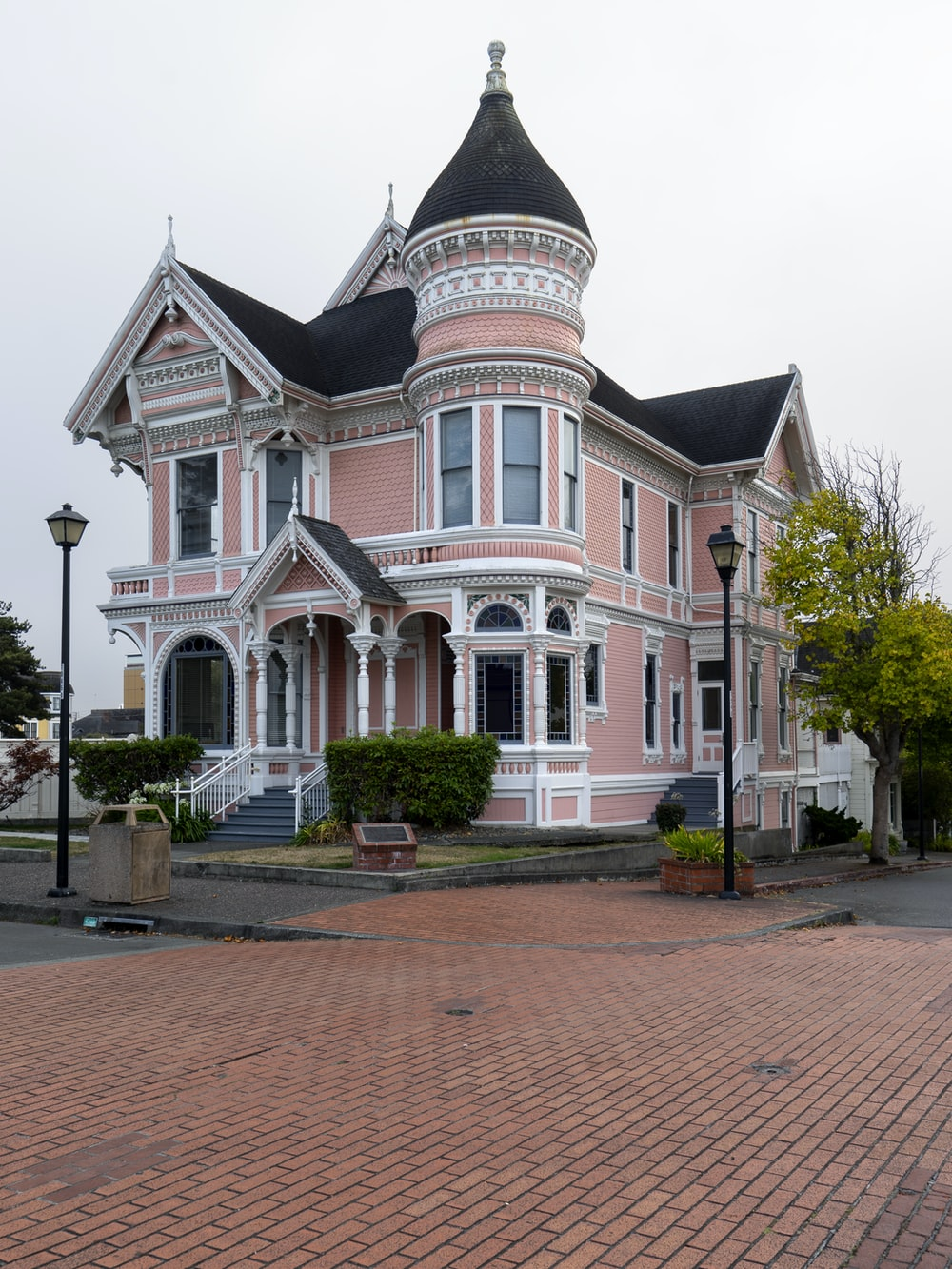 white and pink house near lampposts and road during day