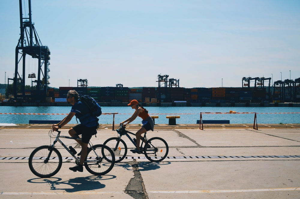 two people cycling near body of water during daytime