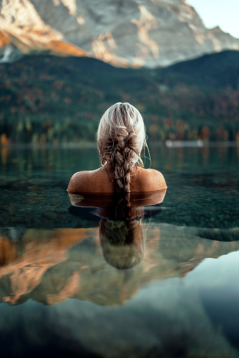 woman half submerge in the water facing mountain at daytime