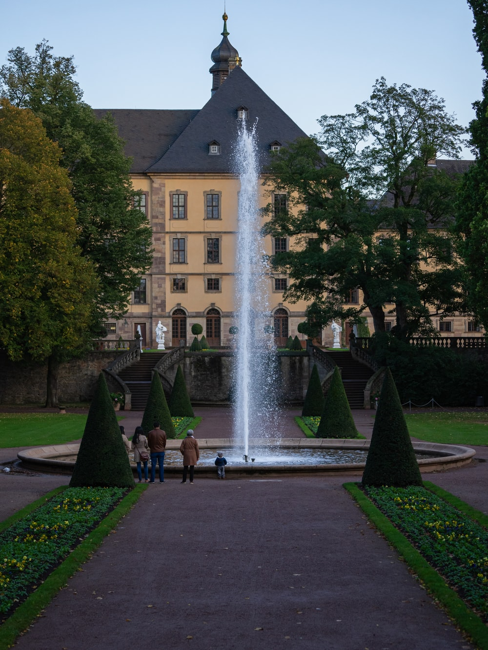 photography of people standing beside fountain during daytime