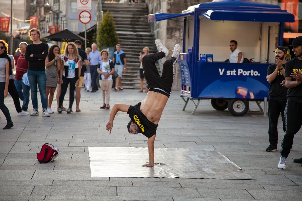 man wearing black and yellow printed crew-neck t-shirt doing stunts a and people watching him