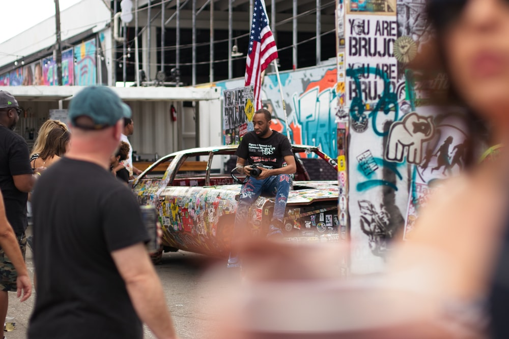 man sitting on car hood near people