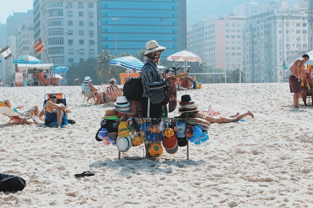 man carrying hats on rod