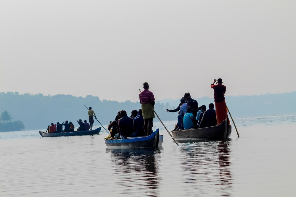 people riding rowboats during daytime