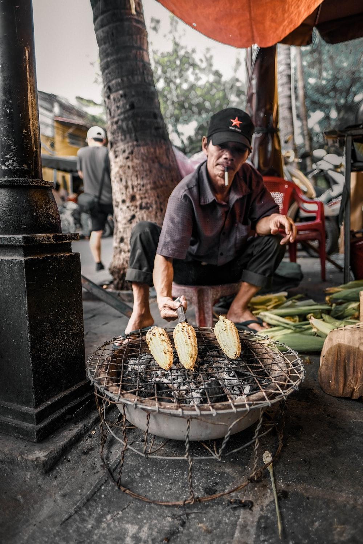 man grilling corns on firepit